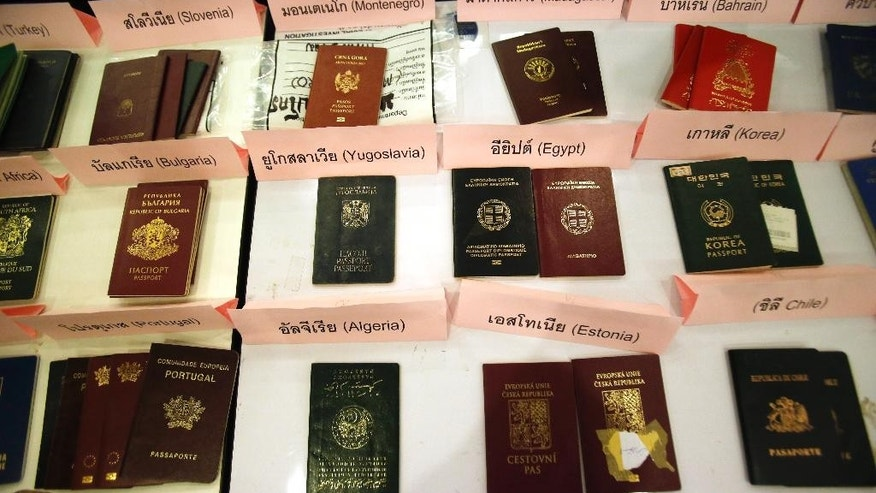 Department of Special Investigation officers display stolen passports during a press conference at the Department of Special Investigation Headquarters in Bangkok,Thailand Wednesday, March. 18, 2015. The Thai Department of Special Investigation on Wednesday announced they had arrested an Iranian man who allegedly was a ringleader in a passport forgery network, and confiscated more than 1,000 stolen passports. (AP Photo/Sakchai Lalit)
