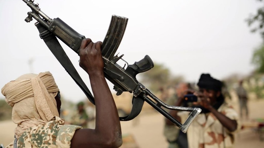 A Chadian soldier raises his automatic weapon to have his picture taken by another soldier  in the Nigerian city of Damasak, Nigeria, Wednesday March 18, 2015. Damasak was flushed of Boko Haram militants last week, and is now controlled by a joint Chadian and Nigerien force. (AP Photo/Jerome Delay)