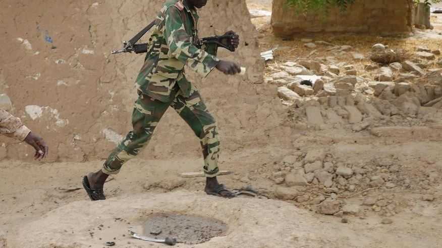 A Chadian soldiers walks in the city of Damasak, Nigeria, Wednesday, March 18, 2015. Damasak was flushed of Boko Haram militants last week, and is now controlled by a joint Chadian and Nigerien force. (AP Photo/Jerome Delay)