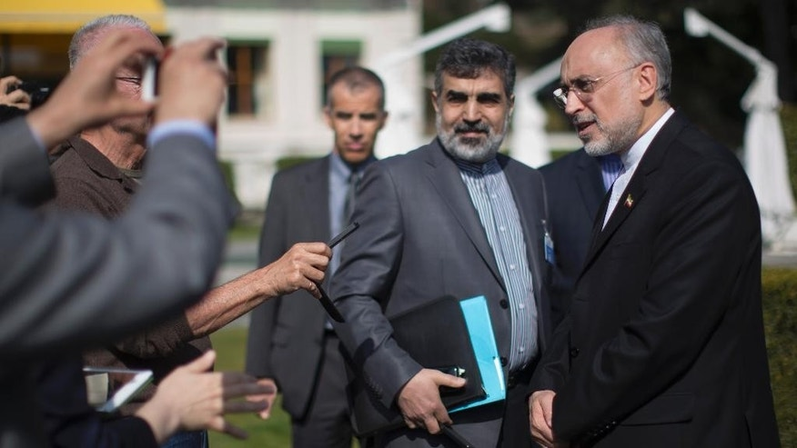 Iran's nuclear chief Ali Akbar Salehi, right, speaks to journalists during negotiations with the United States over Iran's nuclear program in Lausanne, Switzerland, Tuesday, March 17, 2015. Top U.S. and Iranian diplomats returned to talks on Tuesday, trying to resolve differences blocking a deal that would curtail Iran's nuclear program and ease sanctions on the country. (AP Photo/Brian Snyder, Pool)