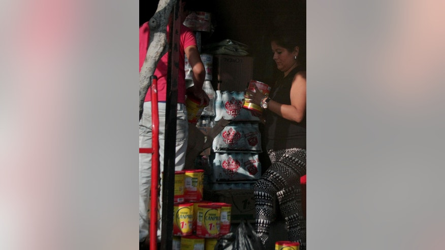 In this Saturday, March 7, 2015 photo, a customer buys milk smuggled from Venezuela at a market in Cucuta, Colombia. In recent months, as shortages in Venezuela have worsened, the government has taken a number of steps to stem the flow of contraband along the porous 1,400-mile (2,200 kilometers) border, including closing crossings at night, deploying more troops and ramping up jail sentences for anyone caught smuggling. President Nicolas Maduro almost daily blames the smuggling as a tool used by his enemies and business elites fighting an economic war to oust his socialist government from power. (AP Photo/Eliecer Mantilla)