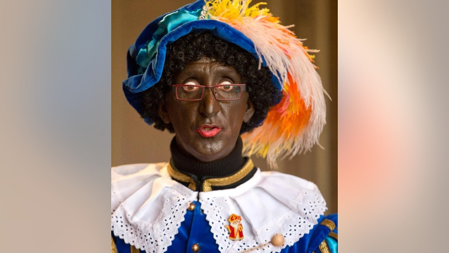 In this Thursday, Nov. 13, 2014 file photo, an actor portraying Zwarte Piet (Black Pete) speaks with children at the House of the Sint in Sint-Niklaas, Belgium. Belgian Foreign Minister Didier Reynders is coming under criticism for appearing with a blackened face at a charity event on Saturday, March 14, 2015, raising questions about Belgium's sensitivity toward racism. Reynders insisted he blackened his face only as part of a century-old tradition that is part of a charity event for the poor. But human rights groups were outraged by his action over the weekend. (AP Photo/Virginia Mayo, File)