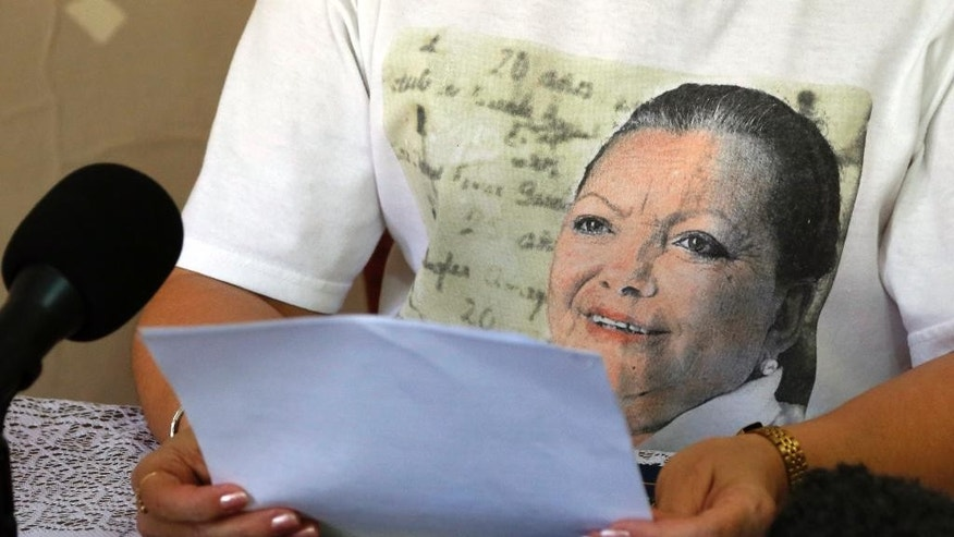 Laura Maria Labrada Pollan, daughter of the late co-founder of Cuba's Ladies in White dissident group, Laura Pollan, on her T-shirt, reads a statement to reporters in Havana, Cuba, Thursday, March 19, 2015. Labrada says she rejects the management of current leader Berta Soler, and the expulsion of group members. She also said that Soler will no longer be able to use her parents' home, which historically has functioned as the Ladies' meeting house and headquarters. (AP Photo/Desmond Boylan)