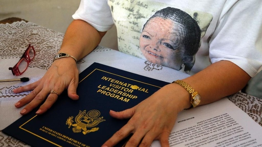 Laura Maria Labrada Pollan, daughter of late co-founder of Cuba's Ladies in White dissident group, Laura Pollan, pictured on her T-shirt, shows a U.S. State Department leadership program diploma after reading a statement to reporters in Havana, Cuba, Thursday, March 19, 2015. Labrada says she rejects the management of current leader Berta Soler, and the expulsion of group members. She also said that Soler will no longer be able to use her parents' home, which historically has functioned as the Ladies' meeting house and headquarters. (AP Photo/Desmond Boylan)