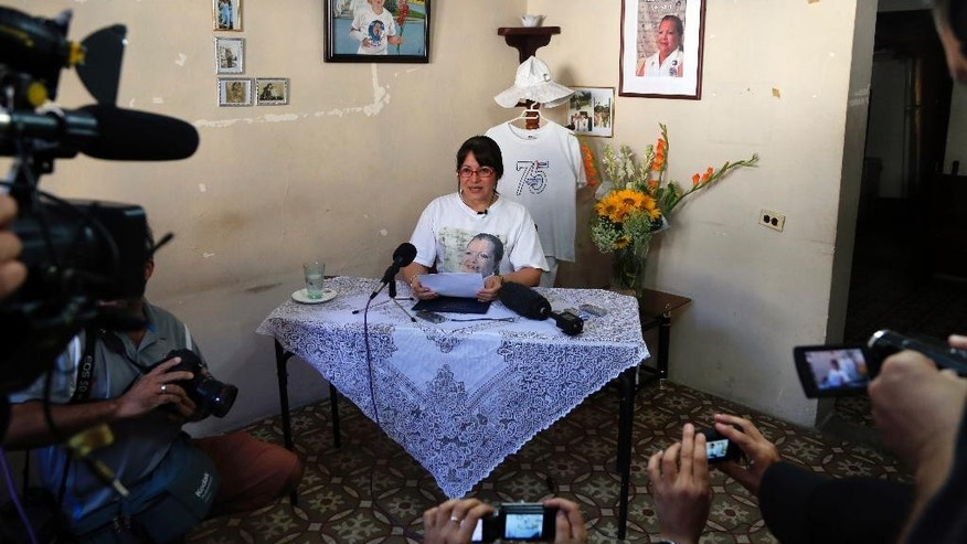 Laura Maria Labrada Pollan, daughter of the late co-founder of Cuba's Ladies in White dissident group, Laura Pollan, reads a statement to reporters in Havana, Cuba, Thursday, March 19, 2015. Labrada says she rejects the management of current leader Berta Soler, and the expulsion of group members. She also said that Soler will no longer be able to use her parents' home, which historically has functioned as the Ladies' meeting house and headquarters. (AP Photo/Desmond Boylan)