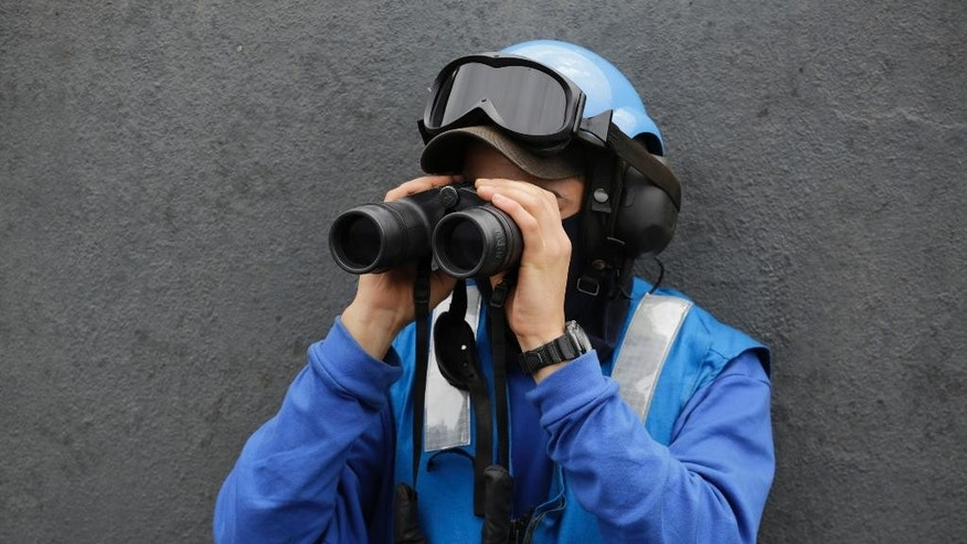 In this Tuesday, March 17, 2015 photo, a French sailor looks with binoculars from the flight deck of the French Navy aircraft carrier Charles de Gaulle in the Persian Gulf. Aircraft aboard the French carrier are flying bombing and reconnaissance missions as part of a U.S.-led coalition targeting Islamic State militants in Iraq. (AP Photo/Hasan Jamali)