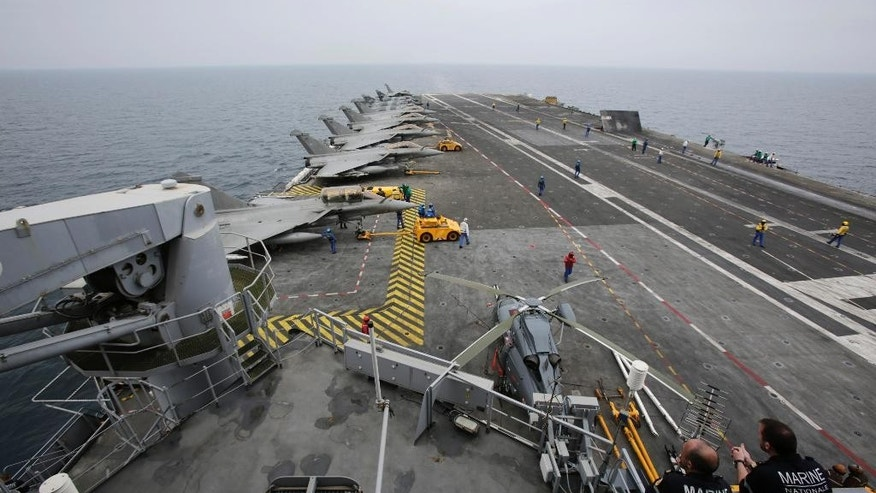 In this Tuesday, March 17, 2015 photo, French sailors work on the flight deck of the French Navy aircraft carrier Charles de Gaulle in the Persian Gulf. Aircraft aboard the French carrier are flying bombing and reconnaissance missions as part of a U.S.-led coalition targeting Islamic State militants in Iraq. (AP Photo/Hasan Jamali)
