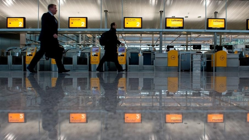 Airline passengers walk past empty check-in counters at the airport in Munich, Germany, Thursday, March 19,  2015. The Lufthansa pilots went on strike in a dispute centering on the airline's plans to cut transition payments for pilots wanting to retire early, which the union wants to see maintained continues. (AP Photo/dpa, Sven Hoppe)
