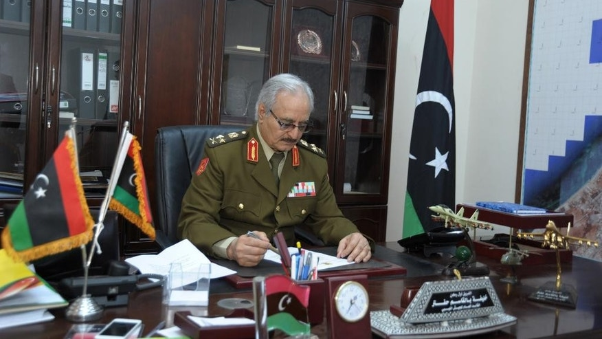 In this Wednesday, March 18, 2015 photo, Gen. Khalifa Hifter, Libya's top army chief, works in his office during a visit by he Associated Press in al-Marj, Libya. Hifter warned Europe of Islamic State militants' infiltration to its territories through the North African nation's long stretch of the Mediterranean coastline, if the West abstained from supporting his forces with arms and ammunition. (AP Photo/Mohammed El-Sheikhy)