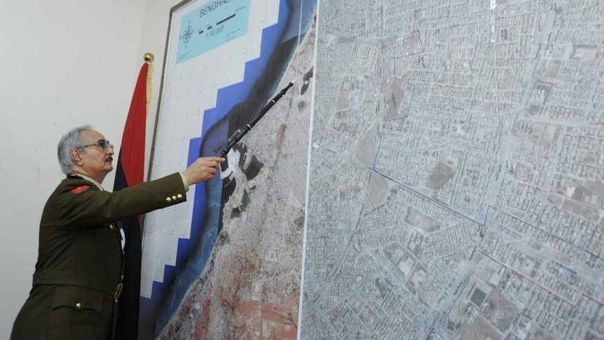 In this Wednesday, March 18, 2015 photo, Gen. Khalifa Hifter, Libya's top army chief, points at a map in his office during an interview with the Associated Press in al-Marj, Libya. Hifter warned Europe of Islamic State militants' infiltration to its territories through the North African nation's long stretch of the Mediterranean coastline, if the West abstained from supporting his forces with arms and ammunition. (AP Photo/ Mohammed El-Sheikhy)