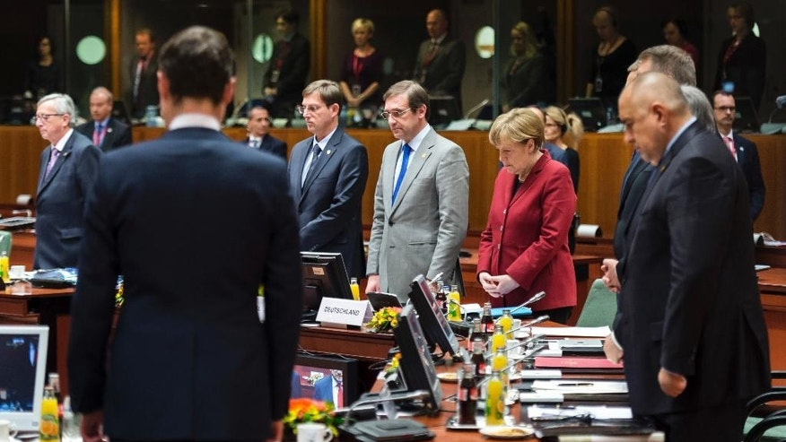 German Chancellor Angela Merkel, center right, observes a moment of silence with other EU leaders during a round table meeting at an EU summit in Brussels on Thursday, March 19, 2015. EU leaders observed a moment of silence during an EU summit on Thursday to remember the victims of a museum attack in Tunisia that took place on Wednesday. (AP Photo/Geert Vanden Wijngaert)