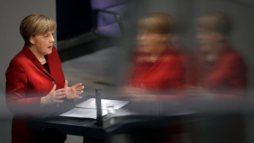 German Chancellor Angela Merkel gestures during her speech as part of a meeting of the German federal parliament, Bundestag,  in Berlin, Germany, Thursday, March 19, 2015. The reflections are caused by windows at the visitors tribune. (AP Photo/Michael Sohn)