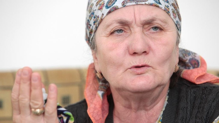 In this photo taken on Wednesday, March 18, 2015, Zulai Gubasheva, the mother of two suspects in the slaying of Russian opposition leader Boris Nemtsov, gestures, during an interview with the Associated Press in the town of Malgobek, Ingushetia, Russia. The mother of two suspects in the slaying of Russian opposition leader Boris Nemtsov says is certain they didn't do it. Anzor and Shagid Gubashev are among five men, all ethnic Chechens, accused in the Feb. 27 killing. (AP Photo/Musa Sadulayev)