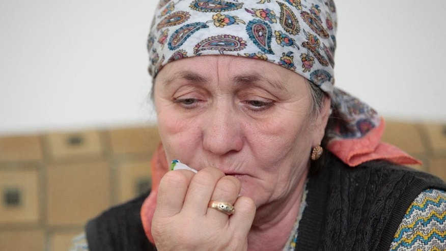 In this photo taken on Wednesday, March 18, 2015, Zulai Gubasheva, the mother of two suspects in the slaying of Russian opposition leader Boris Nemtsov, cries during an interview with the Associated Press in the town of Malgobek, Ingushetia, Russia. The mother of two suspects in the slaying of Russian opposition leader Boris Nemtsov says is certain they didn't do it. Anzor and Shagid Gubashev are among five men, all ethnic Chechens, accused in the Feb. 27 killing. (AP Photo/Musa Sadulayev)