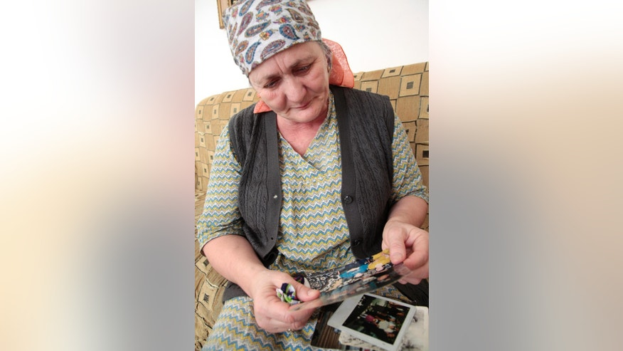 In this photo taken on Wednesday, March 18, 2015, Zulai Gubasheva, the mother of two suspects in the slaying of Russian opposition leader Boris Nemtsov, looks at family photos,  during an interview with the Associated Press in the town of Malgobek, Ingushetia, Russia. The mother of two suspects in the slaying of Russian opposition leader Boris Nemtsov says is certain they didn't do it. Anzor and Shagid Gubashev are among five men, all ethnic Chechens, accused in the Feb. 27 killing. (AP Photo/Musa Sadulayev)