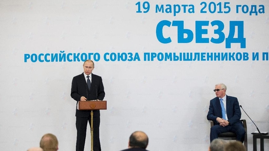 "Russian President Vladimir Putin, left, speaks during a business forum in Moscow, Russia, Thursday, March 19, 2015. Putin has urged a gathering of Russia's billionaires and business leaders to return their capital to Russia and suggested that funds kept abroad could be frozen. The sign reads ""19 of March 2015 year. A congress of the Russian Union of Industrialists and Entrepreneurs."" (AP Photo/Pavel Golovkin)"