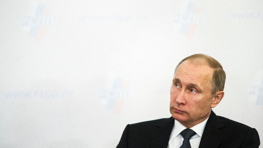 Russian President Vladimir Putin attends a business forum in Moscow, Russia, Thursday, March 19, 2015. Putin has urged a gathering of Russia's billionaires and business leaders to return their capital to Russia and suggested that funds kept abroad could be frozen. (AP Photo/Pavel Golovkin)