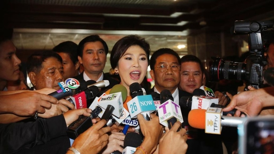 In this Jan. 9, 2015 photo, Thailand's former Prime Minister Yingluck Shinawatra, center, talks to reporters on her arrival at parliament in Bangkok, Thailand. Thailand's Supreme Court announced Thursday, March 19, 2015 that Yingluck will stand trial for negligence related to a rice subsidy program spearheaded by her ousted government that lost billions of dollars, a move likely to deepen the long-running political crisis in the military-ruled nation.(AP photo/Sakchai Lalit)