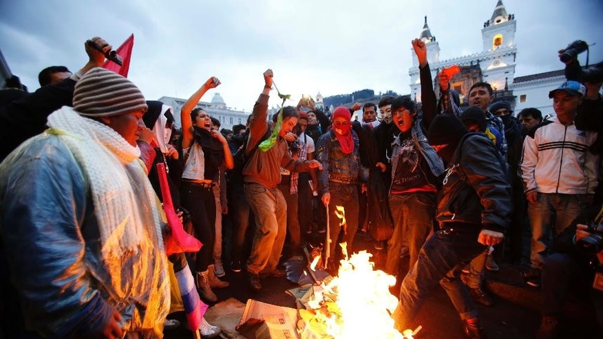 Demonstrators burn an effigy of President Rafael Correa to protest his government in downtown Quito, Ecuador, Thursday, March 19, 2015. Demonstrators are protesting government proposed laws, including a labor law, an initiative on land ownership and a series of constitutional reforms that would allow indefinite reelection for all elected officials. (AP Photo/Dolores Ochoa)