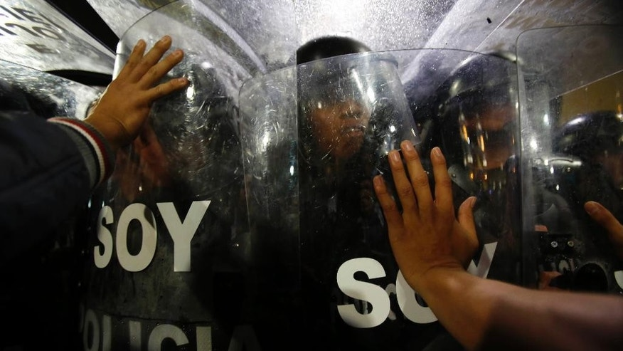 Police block protesters from reaching Independence Plaza, where they wanted to protest the government of President Rafael Correa outside the presidential palace, in downtown Quito, Ecuador, Thursday, March 19, 2015. Demonstrators are protesting government proposed laws, including a labor law, an initiative on land ownership and a series of constitutional reforms that would allow indefinite reelection for all elected officials. (AP Photo/Dolores Ochoa)