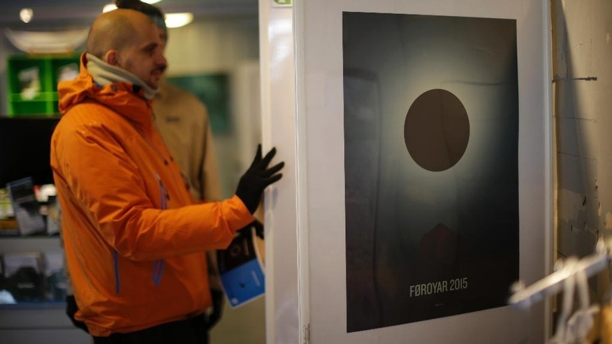 A visitor looks at solar eclipse posters displayed for sale at the tourist office, in Torshavn, the capital city of the Faeroe Islands, Wednesday, March 18, 2015.  The Faeroe Islands, a semi-autonomous Danish archipelago, and Svalbard, a Norwegian archipelago in the Arctic Ocean, are the only two places in the world where, cloud cover permitting, a total solar eclipse can be viewed from land on Friday morning.  (AP Photo/Matt Dunham)
