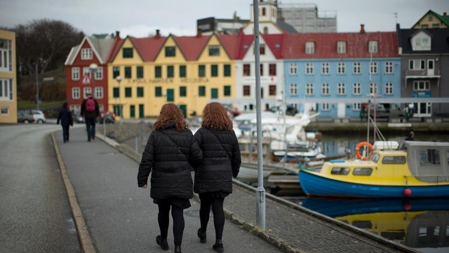 Two women, walk beside the harbor, in Torshavn, the capital city of the Faeroe Islands, Wednesday, March 18, 2015.  The Faeroe Islands, a semi-autonomous Danish archipelago, and Svalbard, a Norwegian archipelago in the Arctic Ocean, are the only two places in the world where, cloud cover permitting, a total solar eclipse can be viewed from land on Friday morning.  (AP Photo/Matt Dunham)
