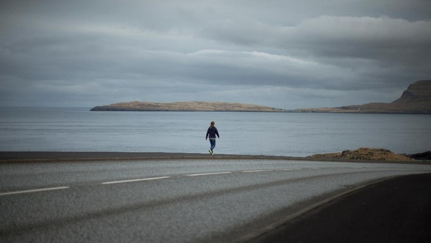 A woman walks along a coastal road in Torshavn, the capital city of the Faeroe Islands, Wednesday, March 18, 2015.  The Faeroe Islands, a semi-autonomous Danish archipelago, and Svalbard, a Norwegian archipelago in the Arctic Ocean, are the only two places in the world where, cloud cover permitting, a total solar eclipse can be viewed from land on Friday morning.  (AP Photo/Matt Dunham)