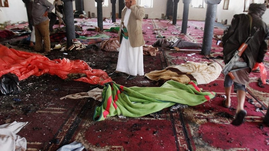 People stand amid bodies covered with blankets in a mosque after a suicide attack during the noon prayer in Sanaa, Yemen, Friday, March 20, 2015. Triple suicide bombers hit a pair of mosques crowded with worshippers in the capital on Friday, causing heavy casualties, according to witnesses. The attackers targeted mosques frequented by Shiite rebels, who have controlled the capital since September. (AP Photo/Hani Mohammed)