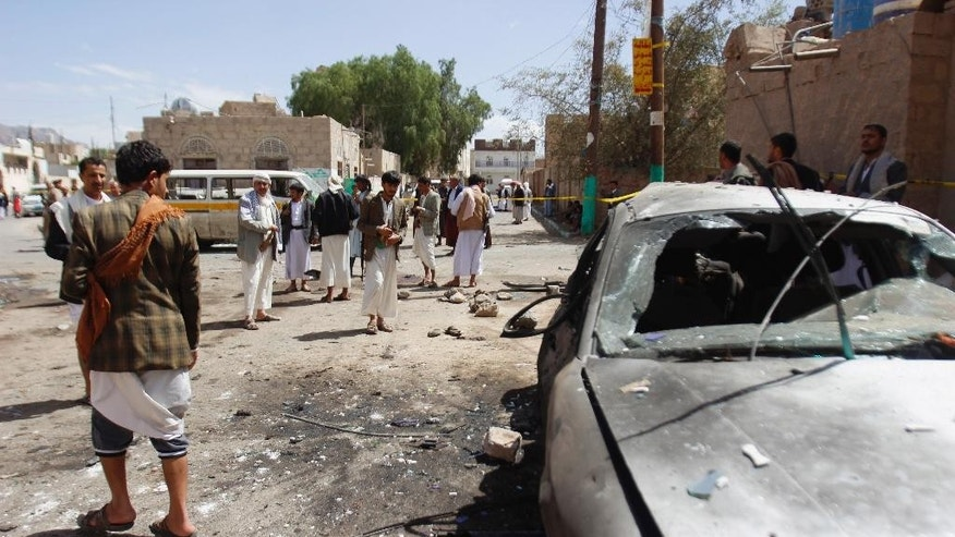 Shiite rebels, known as Houthi, stand near a damaged car after a bomb attack in a mosque in Sanaa, Yemen, Friday, March 20, 2015. Triple suicide bombers hit a pair of mosques crowded with worshippers in the Yemeni capital, Sanaa, on Friday, causing heavy casualties, according to witnesses. The attackers targeted mosques frequented by Shiite rebels, who have controlled the capital since September. (AP Photo/Hani Mohammed)