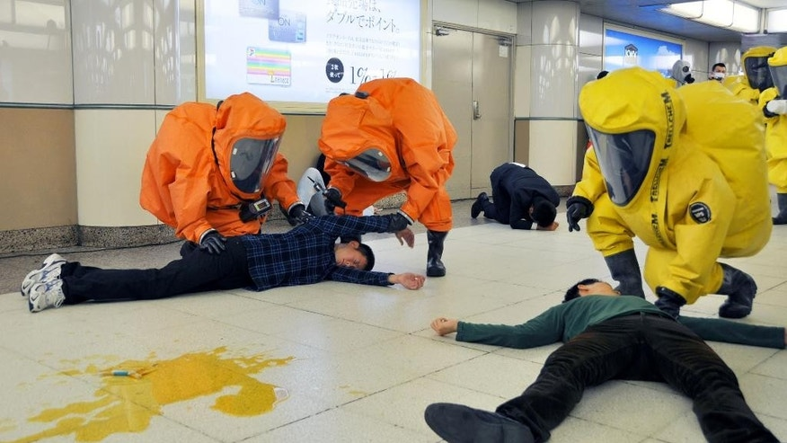 Rescuers wearing protective gear make a rescue operation during a drill against a sarin gas attack, marking the 20th anniversary of the poison gas attack in Japan, at a train station in Tokyo, Friday, March 20, 2015. The release of sarin gas into the Tokyo subways by the Aum Shinrikyo doomsday cult killed 12 people on March 20, 1995. (AP Photo/Kyodo News) JAPAN OUT, MANDATORY CREDIT