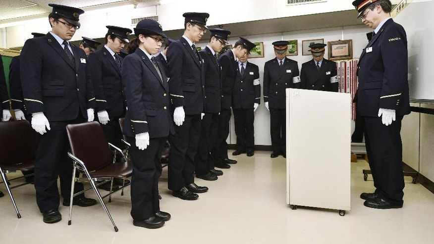Tokyo subway workers offer silent prayer at Kasumigaseki station Friday, March 20, 2015, marking the 20th anniversary of a poison gas attack in Japan. The release of sarin gas into the Tokyo subways by the Aum Shinrikyo doomsday cult killed 12 people on March 20, 1995.  (AP Photo/Kyodo News) JAPAN OUT, MANDATORY CREDIT
