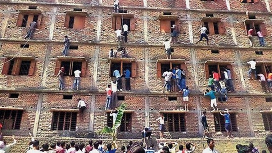 In this file photo, Indians climb the wall of a building to help students appearing in an examination in Hajipur, in the eastern Indian state of Bihar.