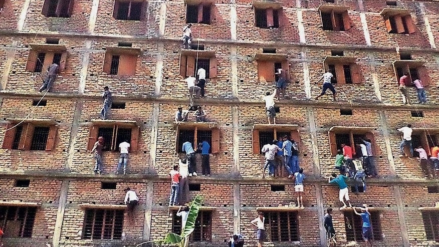 FILE - In this Wednesday, March 18, 2014 file photo, Indians climb the wall of a building to help students appearing in an examination in Hajipur, in the eastern Indian state of Bihar. Education authorities in eastern India say 600 high school students have been expelled after they were found to have cheated on pressure-packed 10th grade examinations. (AP Photo/Press Trust of India, File) INDIA OUT