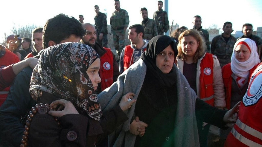 FILE - In this Sunday Feb. 9, 2014, file photo, provided by the Syrian official news agency SANA, Syrian army soldiers, top background, look on as two women walk towards a bus to evacuate the battleground city of Homs, Syria, where a Syrian Red Crescent official says around 300 more people were evacuated from besieged rebel-held neighborhoods in the area. A report due out the week of March 23, 2015, says the number of Syrian people living in besieged areas is at least three times as high as the official estimate and is closer to 650,000, while offering a graphic accounting of hundreds of deaths in communities that the world has struggled to reach for years. (AP Photo/SANA, File)