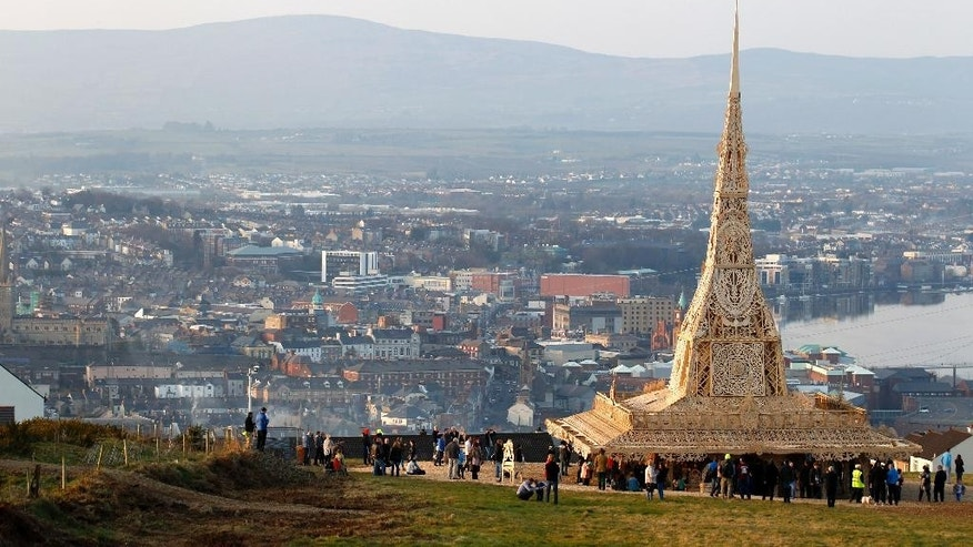 In this image taken Wednesday March 18, 2015, people visit the intricately hand crafted wooden tower, on a hill overlooking Londonderry, Northern Ireland.  Attracting thousands of people to the 72 foot tall (22 meter) wooden tower designed by American sculptor David Best, that is scheduled to be burned to the ground Saturday night. In a region normally marked by divisions, and where bonfires are normally burned as acts of sectarian division, this ornate wooden tower is attracting both Protestant and Catholic admiration, in an atmosphere of harmony.  (AP Photo/Peter Morrison)
