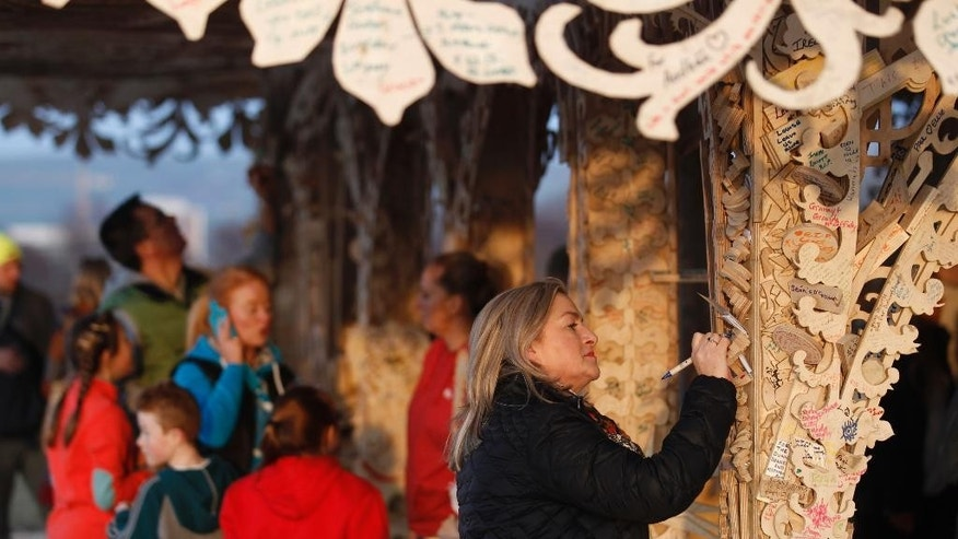 In this Photo taken Wednesday March 18, 2015, a woman writes a message on the intricately hand crafted wooden tower, on a hill overlooking Londonderry, Northern Ireland.  Attracting thousands of people to write messages, the 72 foot tall (22 meter) wooden tower designed by American sculptor David Best, is scheduled to be burned to the ground Saturday night. In a region normally marked by divisions, and where bonfires are normally burned as acts of sectarian division, this ornate wooden tower is attracting both Protestant and Catholic admiration, in an atmosphere of harmony. (AP Photo/Peter Morrison)