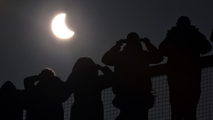 People watch as a solar eclipse begins over the Eden Project near St Austell in Cornwall, England Friday March 20, 2015. An eclipse is darkening parts of Europe on Friday in a rare solar event that won't be repeated for more than a decade.  (AP Photo/PA, Ben Birchall)  UNITED KINGDOM OUT: NO SALES: NO ARCHIVE: