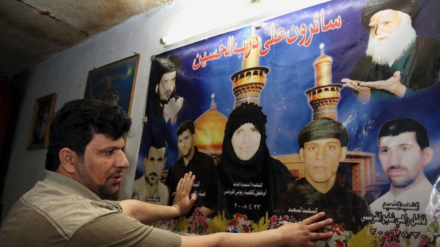 Alaa al-Qureishi shows a religious poster honoring his mother, three brothers and a brother-in-law, who were killed in 2006 and 2007, at his house in Baghdad, Iraq, Friday, March 20, 2015. Twelve years after the U.S. invaded Iraq to topple Saddam Hussein, the country is still mired in war. Today, many of his fellow Shiites are on the front lines battling the Islamic State group. But al-Qureishi, 37, is sitting this one out. (AP Photo/Karim Kadim)