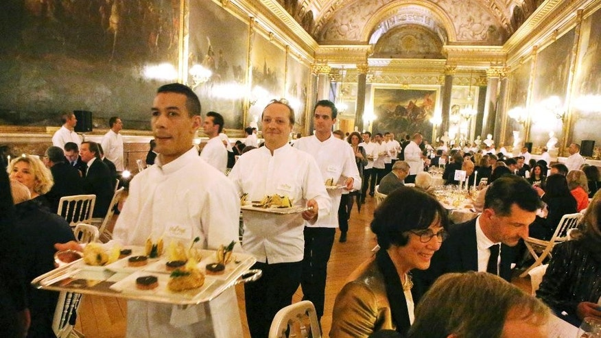 "A dinner prepared by French famous chefs is served to guests, in the Battles Gallery at the Versailles Palace, west of Paris, Thursday March 19, 2015. The world was a symphony of popping champagne corks Thursday night, as over a thousand chefs across 5 continents celebrated the delights of French gastronomy in the first worldwide ""Good France"" event. (AP Photo/Remy de la Mauviniere)"