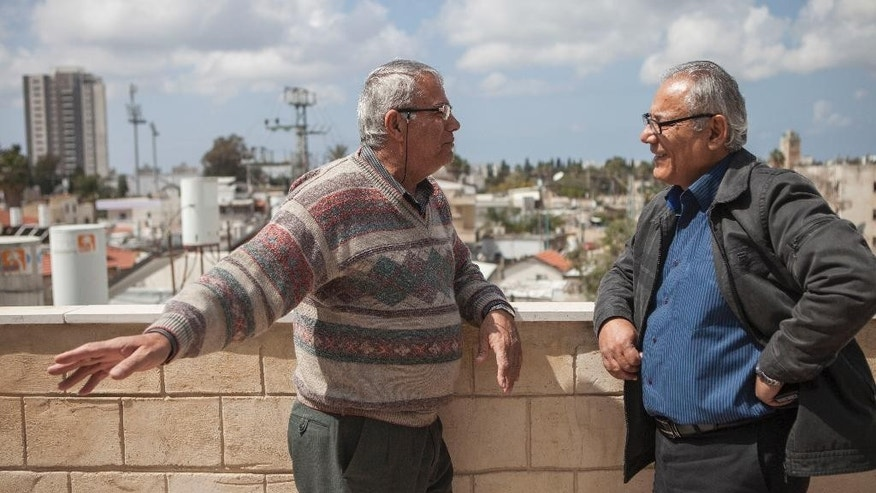 In this photo taken Thursday, March 19, 2015, Fayez Mansour, 65, and Awad Khoury, 65, speak on a rooftop in the mixed Jewish-Arab city of Ramla, Israel. Mansour, a member of the Ramla city council, said this week's parliament election in Israel has left Israel's Arab citizens with more cloud, but also a greater sense of exclusion, after Prime Minister Benjamin Netanyahu rallied his supporters by portraying Arab voters as a threat. (AP Photo/Dan Balilty)