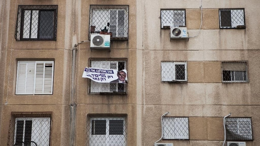 In this photo taken Thursday, March 19, 2015, an election billboard for Israeli Prime Minister Benjamin Netanyahu hangs on a building in the Jewish-Arab city of Ramla, Israel, Israeli Arabs emerged from this week's parliament election with more political clout but also a greater sense of exclusion, after Prime Minister Benjamin Netanyahu rallied his supporters by portraying Arab voters as a threat. (AP Photo/Dan Balilty)