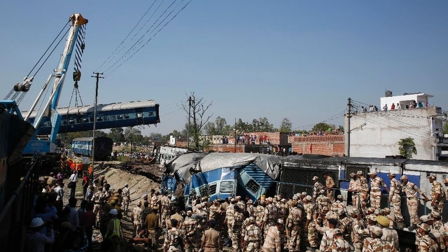 Rescue workers gather at the site of a train accident near Bachhrawan village in the northern Indian state of Uttar Pradesh, Friday, March 20, 2015. Police and rescue workers used gas cutters to rip apart the wreckage to find people who were feared to be trapped after three coaches of a passenger train derailed in northern India. (AP Photo/Rajesh Kumar Singh)