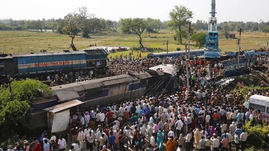 Rescue workers and others gather at the site of a train accident near Bachhrawan village in the northern Indian state of Uttar Pradesh, Friday, March 20, 2015. Police and rescue workers used gas cutters to rip apart the wreckage to find people who were feared to be trapped after three coaches of a passenger train derailed in northern India. (AP Photo/Rajesh Kumar Singh)