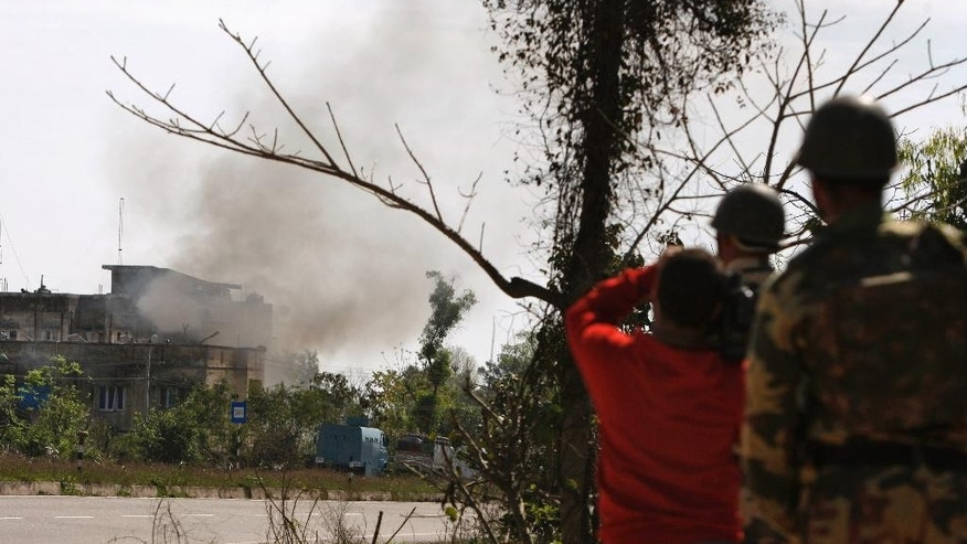 Smoke erupts from Rajbagh police station following a gunfight between suspected militants and security forces in Kathua district, about 80 kilometers (50 miles) south of Jammu, India, Friday, March 20, 2015. Suspected rebels wearing army uniforms stormed the Indian police station in Kashmir, sparking a four-hour gun battle near the border between Indian- and Pakistani-controlled parts of the disputed Himalayan region. (AP Photo/Channi Anand)
