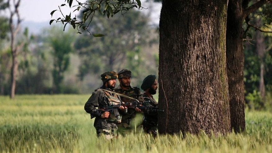 Indian army soldiers take position behind a tree as they watch a gun battle between suspected militants and security forces in Kathua district, about 80 kilometers (50 miles) south of Jammu, India, Friday, March 20, 2015. Suspected rebels wearing army uniforms stormed an Indian police station in Kashmir, sparking a four-hour gun battle near the border between Indian- and Pakistani-controlled parts of the disputed Himalayan region. (AP Photo/Channi Anand)