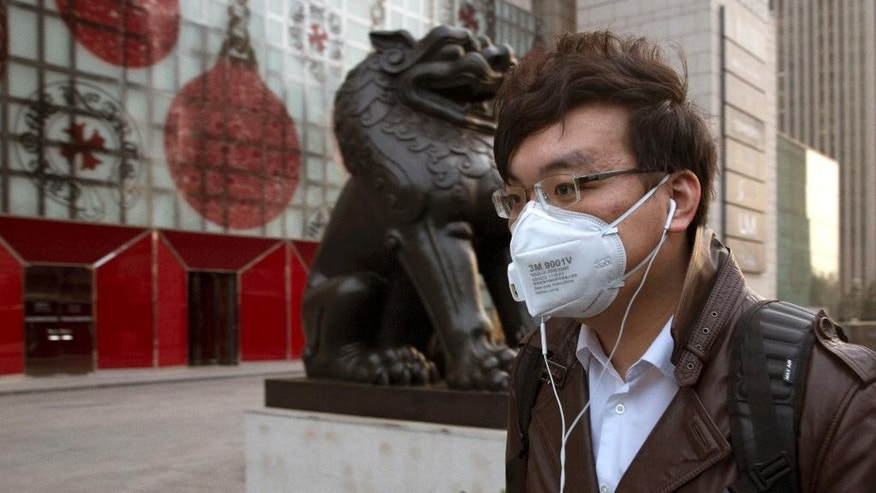 A man wears a mask on the streets of Beijing Friday, March 20, 2015. A U.S. envoy for climate change said Friday that China and the U.S. are working more closely than ever ahead of a conference this year in Paris that raises hopes for a global plan to cut greenhouse emissions. (AP Photo/Ng Han Guan)