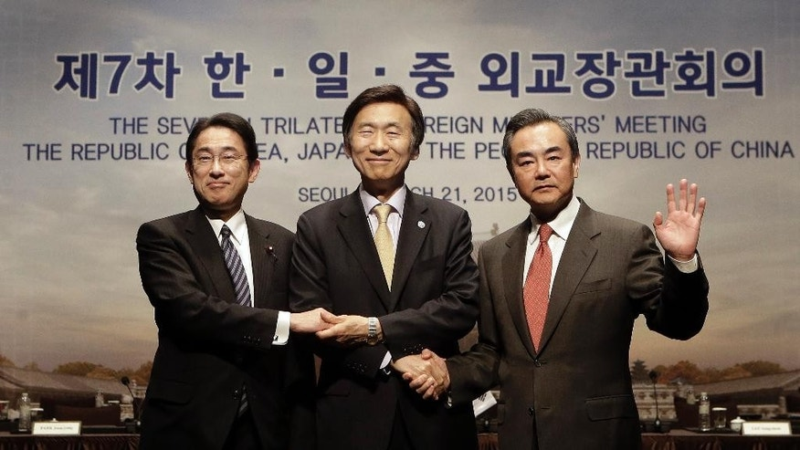 From right, Chinese Foreign Minister Wang Yi, South Korean Foreign Minister Yun Byung-se and Japanese Foreign Minister Fumio Kishida pose during the 7th trilateral foreign ministers' meeting in Seoul, South Korea,  Saturday, March 21, 2015. (AP Photo/Ahn Young-joon. Pool)