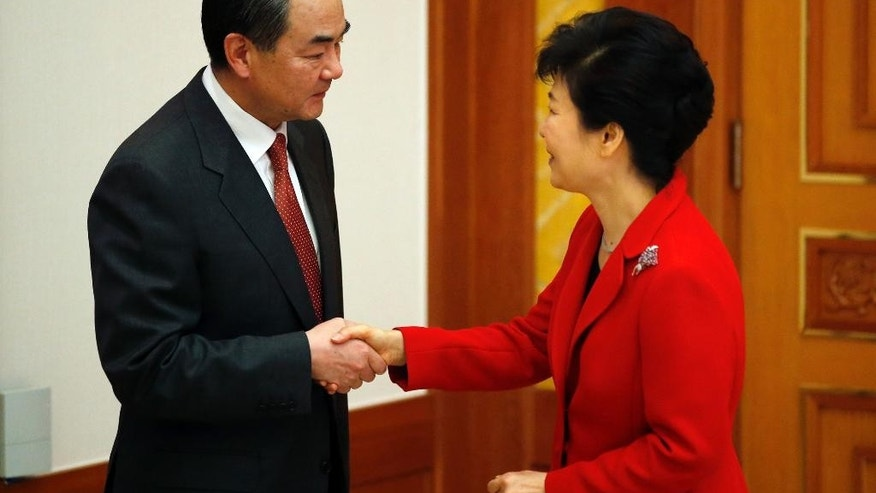 South Korea President Park Geun-hye, right, shakes hands with Chinese Foreign Minister Wang Yi, left, during their meeting at the Presidential Blue House in Seoul Saturday, March 21, 2015.   The foreign ministers of South Korea, China and Japan will meet for the first time in three years this weekend after bitter disputes over history and territory drastically scaled back high-level contacts and even raised security fears. (AP Photo/Kim Hong-Ji, Pool)