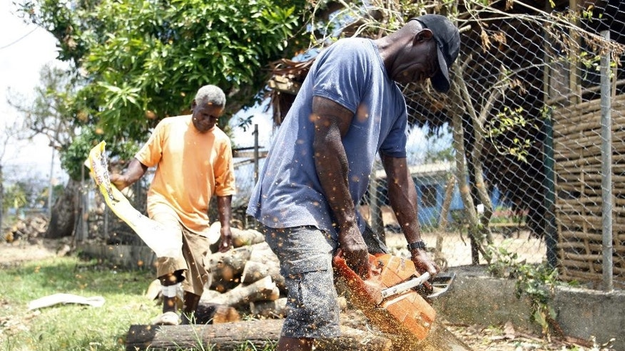 A man uses a chainsaw to cut trees on the side of the road in Port Vila, Vanuatu, on Saturday, March 21, 2015. A week after Cyclone Pam tore through the South Pacific archipelago with winds of 270 kilometers (168 miles) per hour, people are focused on the task of rebuilding. (AP Photo/Nick Perry)