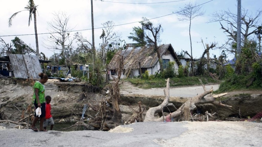 People walk past a washed-out bridge on the island of Efate, Vanuatu on Saturday, March 21, 2015. A week after Cyclone Pam tore through the South Pacific archipelago with winds of 270 kilometers (168 miles) per hour, people are focused on the task of rebuilding. (AP Photo/Nick Perry)